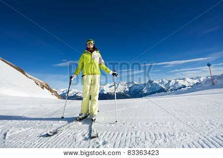 Happy woman in mask skiing on ski-track slone