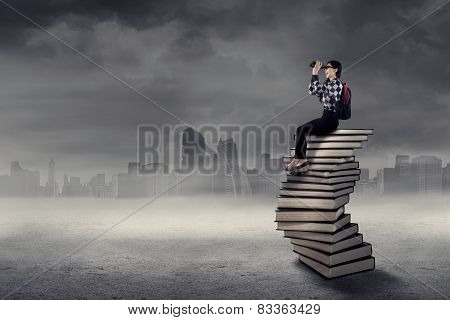 Student Looking Through Binoculars Above Book