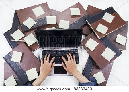 Student Typing With Laptop Around Book