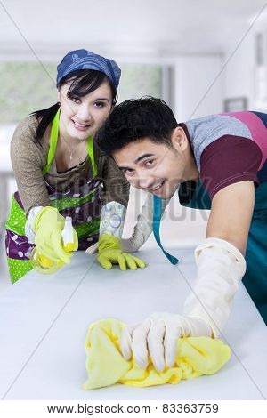 Young Couple Cleaning A Table