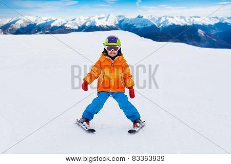 Boy wearing ski mask and helmet skiing on slope