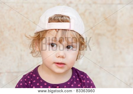 Curious Cute Blond Baby Girl In White Baseball Cap