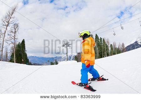 Boy from the back in ski mask and helmet skiing