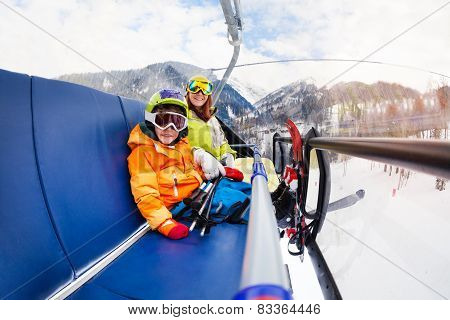 Little boy and mother on ski lift chair