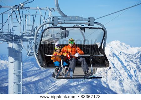 Father and boy sit in ski lift over mountains