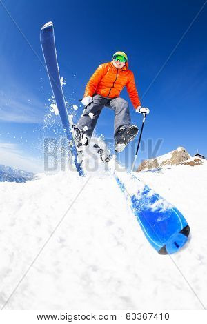 Young man in a jump while skiing view from below