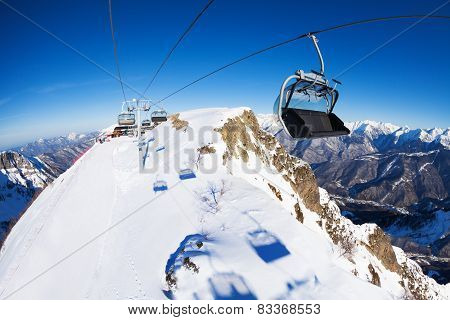 Ski lift with chairs, ropeway over mountain range