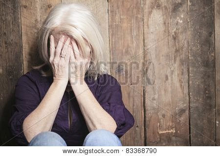 A depress senior person with wood background