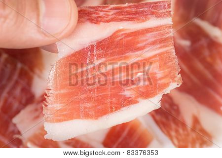 Top view of caucasian man hand taking Serrano ham slice