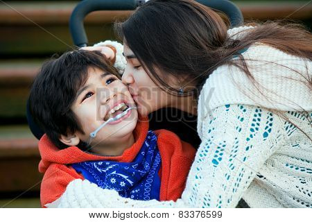 Big Sister Kissing Disabled Little Brother Seated In Wheelchair On Cheek