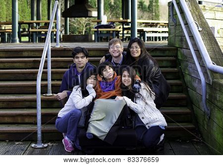 Interracial Family Surrounding Disabled Boy In Wheelchair Outdoors By Stairs, Child Has Cerebral Pal
