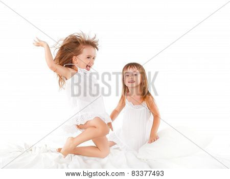 Happy Family .  Kids Twin Sisters Jumping On The Bed, Playing And Laughing