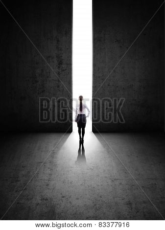 businesswoman against black wall with hole