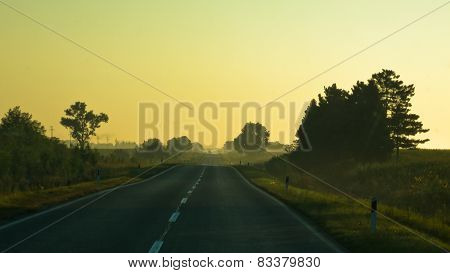 Telephoto of picturesque country road at sunrise