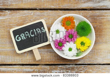 Gracias (which means thank you in Spanish) written on miniature blackboard and colorful Santini flow
