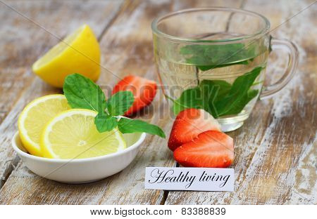 Healthy living card with glass of mint tea, lemon and strawberries