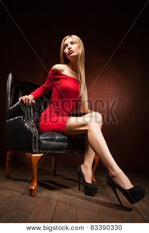 Shot of beautiful woman wearing red dress sitting in armchair