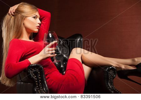 Closeup portrait of  blonde lying in armchair with wine glass