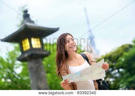 Travel in Tokyo - Asian tourist woman with map searching for directions with the Tokyo Skytree tower in the background. Young chinese adult visiting the city in Japan.