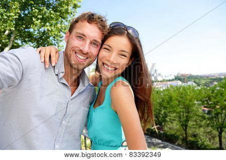 Couple tourists taking travel selfie self-portrait in Madrid park, Spain in summer. Young adults mixed race asian caucasian smiling at smartphone camera for a snapshot during their holidays in Europe.