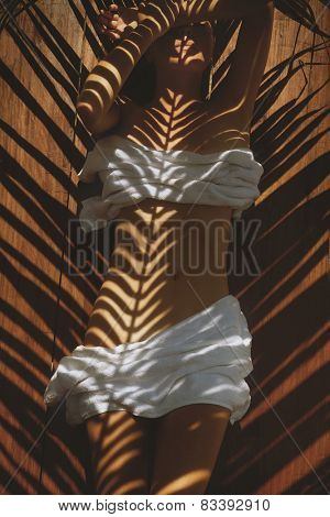 Cropped image of woman in spa with palm leaves reflection on body