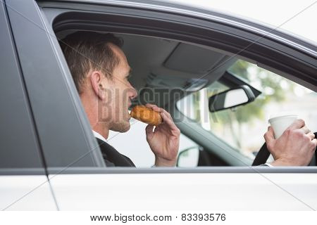 Businessman having coffee and doughnut on the phone in his car