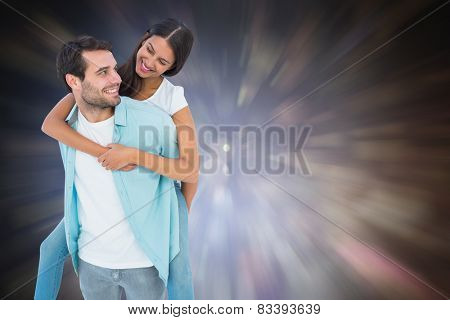 Happy casual man giving pretty girlfriend piggy back against dark abstract light spot design