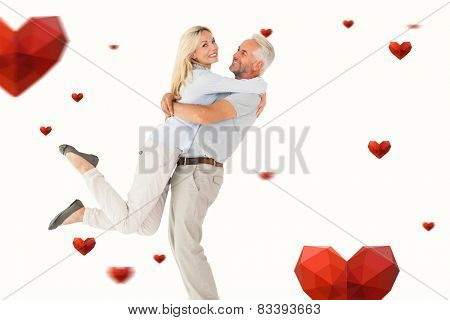 Man picking up his partner while hugging here against hearts