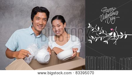 Happy couple unpacking moving boxes against cute valentines message