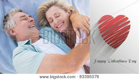 Happy senior couple cuddling on blanket against cute valentines message