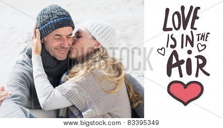 Attractive couple on the beach in warm clothing against love is in the air