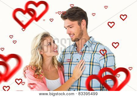 Attractive young couple smiling at each other against hearts