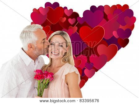 Affectionate man kissing his wife on the cheek with roses against heart