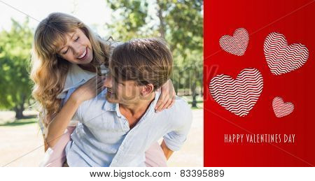 Man giving his pretty girlfriend a piggy back in the park smiling at each other against cute valentines message