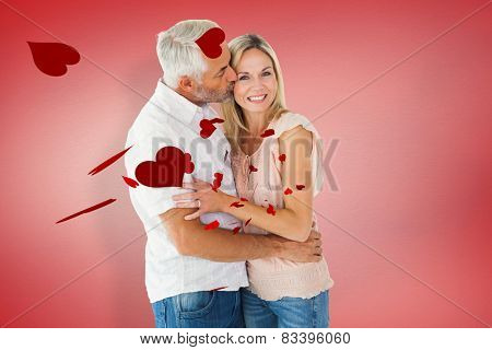 Affectionate man kissing his wife on the cheek against red vignette
