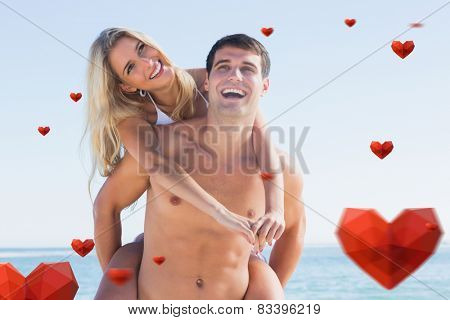 Laughing man giving his pretty girlfriend a piggy back smiling against hearts