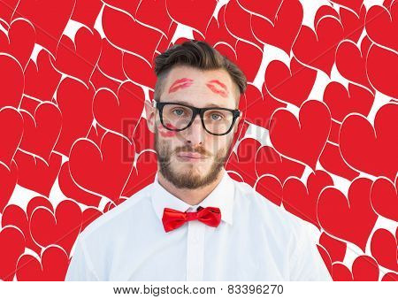 Geeky hipster with kisses on his face against valentines day pattern
