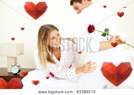 Attentive man giving a rose to his wife against hearts