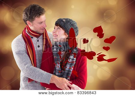 Smiling couple looking at each other against orange abstract light spot design