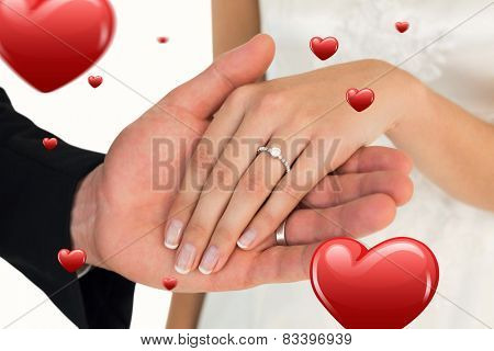 Cropped image of newly wed couple holding hands against hearts