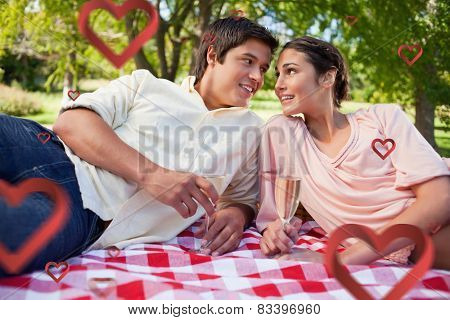 Two friends looking at each other while having a picnic against hearts