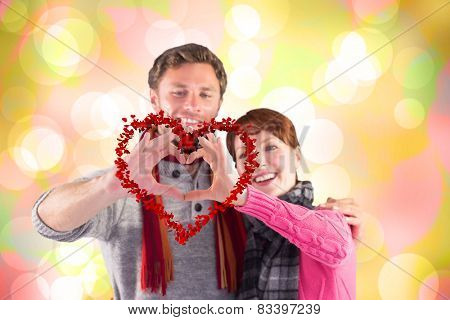 Couple making a heart shape against girly pink and yellow pattern