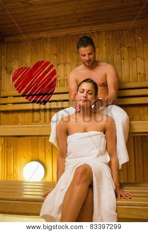 Man giving his girlfriend a neck massage in sauna against red heart