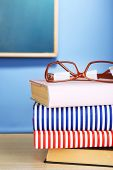 stock photo of bookworm  - Stack of books with glasses on wooden desk - JPG