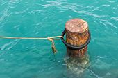 pic of bollard  - Rusty mooring bollard with ship ropes on docks - JPG