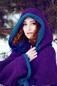 stock photo of auburn  - Mysterious young woman in purple knitted cape with a hood in winter forest - JPG