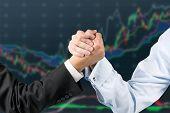 picture of wrestling  - businessmen engaged in arm wrestling on chart background - JPG