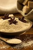 foto of sugar cube  - brown sugar with star anise in a wooden bowl brown sugar cubes in a burlap sack in the background