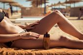 stock photo of body-lotion  - Sensuous slim woman applying suntan lotion oil to her body at the beach - JPG