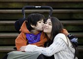 picture of little sister  - Disabled little boy kissing his big sister on cheek while seated in wheelchair - JPG
